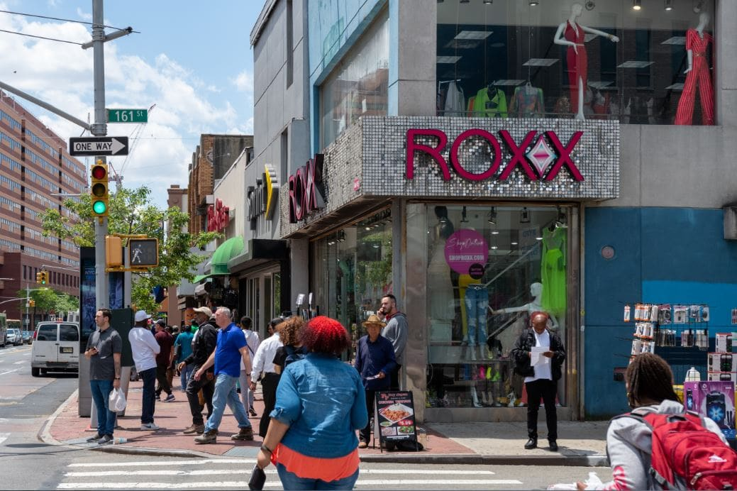 People walking down Jamaica Avenue near the store Roxx